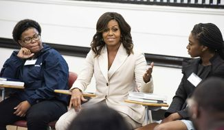 """Michelle Obama, center, speaks with Rayven Peterson and Anta Njie of Morehouse College and Spelman College during a campus visit to Spelman College on Saturday, May 11, 2019, in Atlanta. Mrs. Obama is meeting with students who studied her book """"Becoming"""" as a foundational text of their political science class entitled """"Black Women: Developing Public Leadership Skills"""". (Photo by Paul R. Giunta/Invision/AP)"""