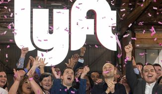"""FILE - In this Friday, March 29, 2019 file photo, Lyft co-founders John Zimmer, front second from left, and Logan Green, front second from right, cheer as they as they ring a ceremonial opening bell in Los Angeles, to mark trading on the Nasdaq exchange under the ticker symbol """"LYFT."""" A fare war between Uber and Lyft has led to billions of dollars in losses for both ride-hailing companies as they fight for passengers and drivers. But in one way it has been good for investors who snatched up the newly public companies' stock: The losses have scared off the competition, giving the leaders a duopoly in almost every American city. (AP Photo/Ringo H.W. Chiu)"""