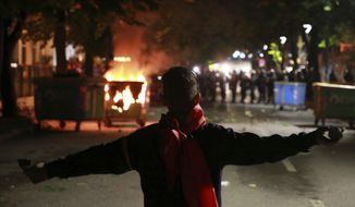 A protester holds stones as police block a road during clashes in Tirana, Saturday, May 11, 2019. Thousands of supporters of the Albania's center-right opposition protested in Tirana Saturday, calling for the left-wing government to resign and for an early parliamentary election. (AP Photo/Hektor Pustina)