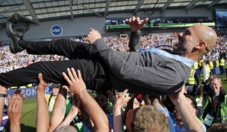 Manchester City coach Pep Guardiola is lifted in the air by the players after the English Premier League soccer match between Brighton and Manchester City at the AMEX Stadium in Brighton, England, Sunday, May 12, 2019. Manchester City defeated Brighton 4-1 to win the championship. (AP Photo/Frank Augstein)