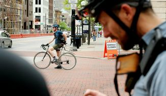 In this Wednesday, May 1, 2019, photo, bike courier Chuck Hootman, back, makes another run while Nate Ziccardi, right, and Kevin Cash, not pictured, wait for him to finish in Columbus, Ohio. Bike couriers once thrived in Columbus, with about 25 of them regularly coursing through the streets, delivering documents to and from attorneys and the courts, among other clients. But electronic filing has taken its toll, and now there are only 4 who do it full-time. (Courtney Hergesheimer/The Columbus Dispatch via AP)