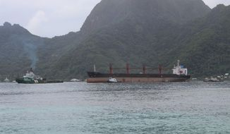 The North Korean cargo ship, Wise Honest, middle, was towed into the Port of Pago Pago in the late morning on Saturday, May 11, 2019, in Pago Pago, American Samoa. The Wise Honest ship was seized by the U.S. because of suspicion it was used to violate international sanctions. It arrived Saturday at the capital of this American territory. (AP Photo/Fili Sagapolutele)