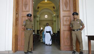 Sri Lankan police officers stand guard at the entrance to St. Lucia's cathedral during a holy mass held to bless victims of the Easter Sunday attacks in Colombo, Sri Lanka, Saturday, May 11, 2019. More than 250 people were killed when suicide bombers struck three churches and three tourist hotels on Easter. Masses at churches were canceled for a second week last Sunday and the reopening of schools was postponed after reports warned of possible new attacks. (AP Photo/Eranga Jayawardena)
