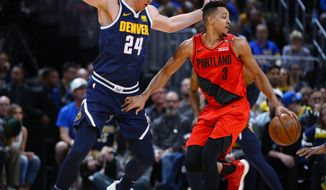 Portland Trail Blazers guard CJ McCollum, right, drives past Denver Nuggets forward Mason Plumlee in the first half of Game 7 of an NBA basketball second-round playoff series Sunday, May 12, 2019, in Denver. (AP Photo/John Leyba)