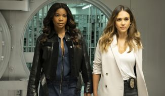 """This image released by Spectrum Originals dhows Gabrielle Union, left, and Jessica Alba in a scene from """"L.A.'s Finest."""" Union and  Alba star in and produce the new police detective series premiering May 13. (Erica Parise/Spectrum Originals via AP)"""