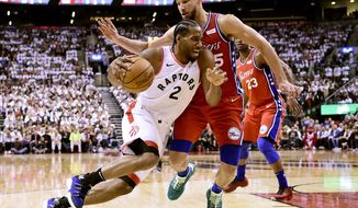 Philadelphia 76ers guard Ben Simmons (25) defends as Toronto Raptors forward Kawhi Leonard (2) drives to the basket during second half NBA Eastern Conference basketball semifinal action in Toronto on Sunday, May 12, 2019. (Frank Gunn/The Canadian Press via AP)