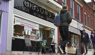 In this Nov. 22, 2017, file photo, pedestrians pass the storefront of Gibson's Food Mart & Bakery in Oberlin, Ohio. (AP Photo/Dake Kang)