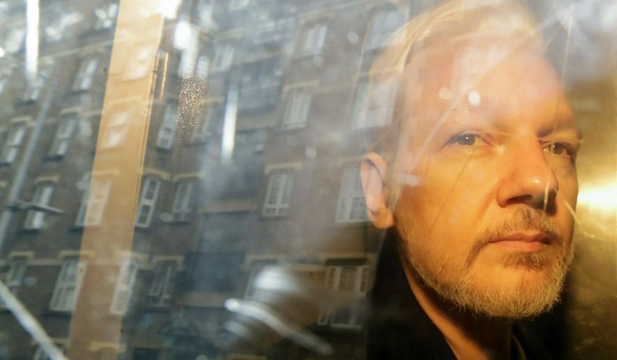 In this Wednesday May 1, 2019 file photo, buildings are reflected in the window as WikiLeaks founder Julian Assange is taken from court, where he appeared on charges of jumping British bail seven years ago, in London. (AP Photo/Matt Dunham)