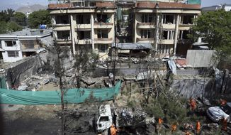 Afghan municipality workers clean a road in front of the damaged buildings, a day after an attack in Kabul, Afghanistan, Thursday, May 9, 2019. Taliban fighters attacked the offices of a U.S.-based aid organization in the Afghan capital on Wednesday, setting off a huge explosion and battling security forces in an assault, the Interior Ministry said. (AP Photo/Rahmat Gul)