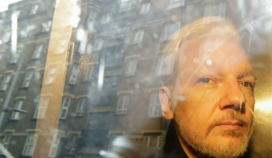 In this Wednesday, May 1, 2019, file photo, buildings are reflected in the window as WikiLeaks founder Julian Assange is taken from court, where he appeared on charges of jumping British bail seven years ago, in London. (AP Photo/Matt Dunham)