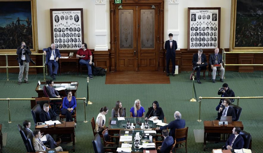 Former gymnasts, seated at center table, Jordan Schwikert, left, Amy Baumann, center, and Tasha Schwikert, right, take part in a hearing about the statute of limitations child sex abuse victims have to sue their abusers, Monday, May 13, 2019, in Austin, Texas. In Texas, lawmakers quietly removed a bill's provision allowing child sex abuse victims to sue institutions and are now shielding the very groups that lobbied them to do so. (AP Photo/Eric Gay)