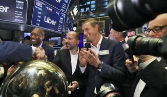 Uber CEO Dara Khosrowshahi center, shakes hands with a trader after his company's initial public offering begins trading at the New York Stock Exchange, Friday, May 10, 2019. He is flanked by Uber's Chief Legal Officer Tony West, left, and board member Ryan Graves, right. (AP Photo/Richard Drew)