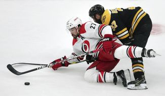 Carolina Hurricanes' Justin Faulk (27) tries to control the puck as he is dropped to the ice by Boston Bruins' Patrice Bergeron, right, during the first period in Game 2 of the NHL hockey Stanley Cup Eastern Conference final series, Sunday, May 12, 2019, in Boston. (AP Photo/Charles Krupa)