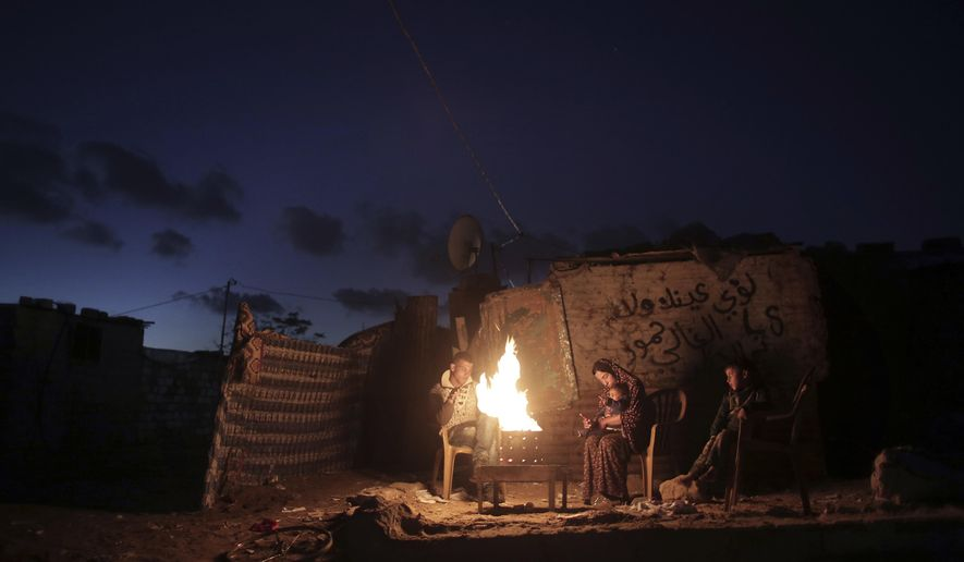 """File - In this Jan. 15, 2017 file photo, a Palestinian family warm up outside their makeshift house during a power cut in Khan Younis in the southern Gaza Strip. Qatar's Foreign Ministry said Tuesday, May 7, 2019, that it will send $480 million to Palestinians in the West Bank and the Gaza Strip after a cease-fire deal ended the deadliest fighting between Israel and Palestinian factions since a 2014 war. A statement from Qatar said $300 million would support health and education programs of the Palestinian Authority, while $180 million would go toward """"urgent humanitarian relief"""" in United Nations programs and toward electricity. (AP Photo/ Khalil Hamra, File)"""