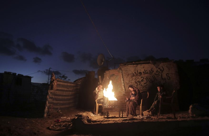 "File - In this Jan. 15, 2017 file photo, a Palestinian family warm up outside their makeshift house during a power cut in Khan Younis in the southern Gaza Strip. Qatar's Foreign Ministry said Tuesday, May 7, 2019, that it will send $480 million to Palestinians in the West Bank and the Gaza Strip after a cease-fire deal ended the deadliest fighting between Israel and Palestinian factions since a 2014 war. A statement from Qatar said $300 million would support health and education programs of the Palestinian Authority, while $180 million would go toward ""urgent humanitarian relief"" in United Nations programs and toward electricity. (AP Photo/ Khalil Hamra, File)"