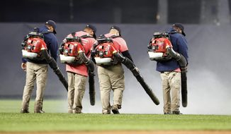 Groundskeeper use leaf blowers to remove water from the field at Yankee Stadium before a baseball game between the New York Yankees and the Baltimore Orioles, Monday, May 13, 2019, in New York. The game was postponed until Wednesday afternoon due to unplayable field conditions. (AP Photo/Kathy Willens)