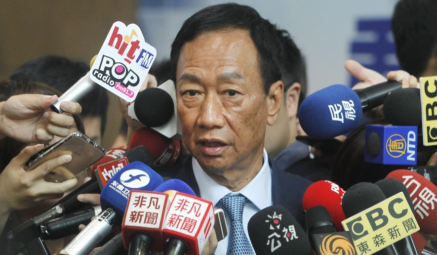 Terry Gou, the head of the world's largest electronics supplier Foxconn, is surrounded by the media after meeting with Nationalist Party chairman Wu Den-yih at the party headquarters in Taipei, Taiwan, Monday, May 13, 2019. Gou plans to run for president of Taiwan, bringing his pro-business and pro-China policies to what is expected to be a crowded field for next year's election. (AP Photo/Chiang Ying-ying)