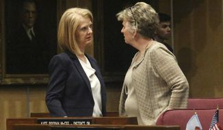 In this April 1, 2019 photo, Arizona Sen. Heather Carter, left, chats with Sen. Kate Brophy McGee during a break in the Arizona Senate in Phoenix. Carter and fellow Republican, Rep. John Allen, are facing off over competing proposals to regulate tobacco and vaping products. (AP Photo/Bob Christie)