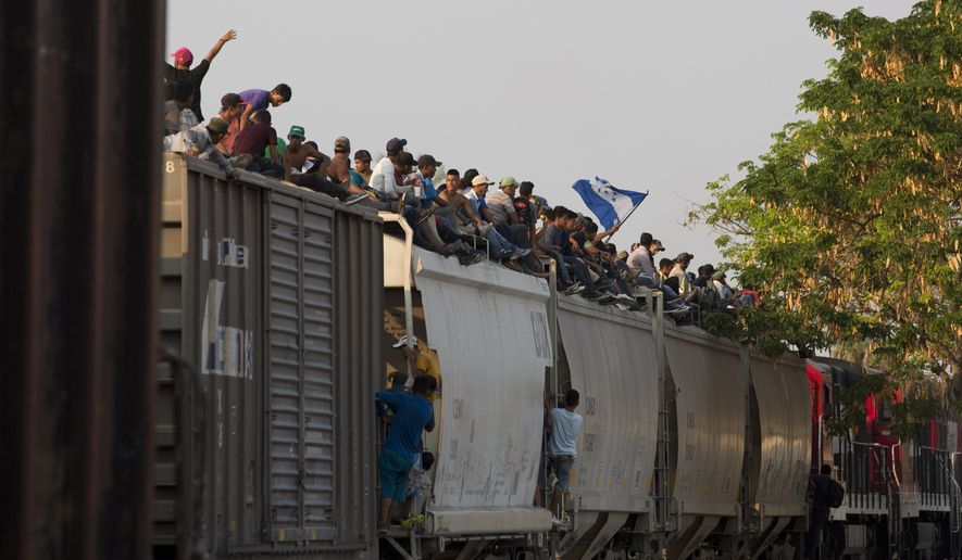 Central American migrants ride atop a freight train during their journey toward the U.S.-Mexico border, in Ixtepec, Oaxaca State, Mexico, Tuesday, April 23, 2019. The once large caravan of about 3,000 people was essentially broken up by an immigration raid on Monday, as migrants fled into the hills, took refuge at shelters and churches or hopped passing freight trains. (AP Photo/Moises Castillo)