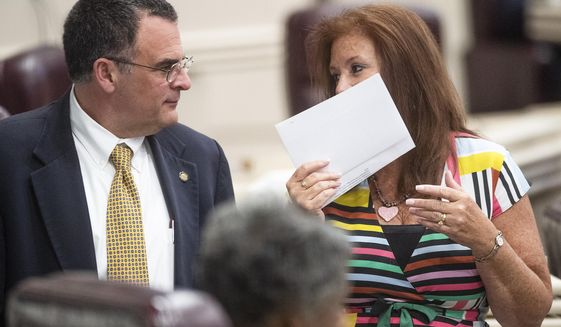 Rep. Terri Collins, right, chats with Rep. Chris Pringle on the house floor at the Alabama Statehouse in Montgomery, Ala., on Tuesday, May 14, 2019. (Mickey Welsh/Montgomery Advertiser via AP)