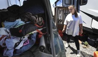 In this May 10, 2019 photo, Pam Peavler works on vacating her FEMA trailer, right, and packing to leave the Sonoma County Fairgrounds RV Park in Santa Rosa, Calif. A trailer park that offered housing for displaced residents following the 2017 wildfires in Sonoma County is closing down.(Kent Porter/The Press Democrat via AP)
