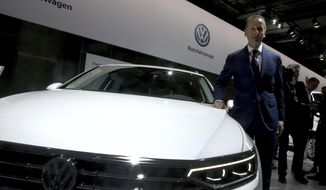 Herbert Diess, CEO of the Volkswagen stock company, poses next to a Volkswagen car prior to the company's annual general meeting in Berlin, Germany, Tuesday, May 14, 2019. (AP Photo/Michael Sohn)