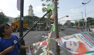 "A Manila City public worker removes the campaign posters, mostly that of incumbent Mayor and former President Joseph ""Erap"" Estrada around the Manila City Hall, a day after the country's midterm elections Tuesday, May 14, 2019 in Manila, Philippines. Estrada lost his third term mayoral bid along with four of his children who ran in local polls, ending his 50-year-dominance in two metropolitan cities in the country. Two of his sons, who ran for senators, are also clinging to the last senate slot in initial results, which were dominated by President Rodrigo Duterte's allies. (AP Photo/Bullit Marquez)"