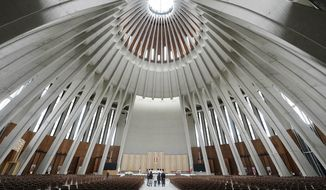 People stand in the Temple of Divine Providence, a major church in the Polish capital, on Monday May 13, 2019. A new documentary about pedophile priests has deeply shaken Poland, one of Europe's most Roman Catholic societies, eliciting an apology from the church hierarchy and prompting one priest to leave the clergy.(AP Photo/Czarek Sokolowski)