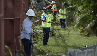 FILE - In this Sept. 23, 2017 file photo, personnel from Liberty Cable work to restore fiber optic lines on the third day after the impact of Maria, a Category 5 hurricane that crossed the island, in Carolina, Puerto Rico. A report issued Tuesday, May 13, 019, by the group Free Press, a consumer activist group, is calling on the U.S. government to investigate the collapse of communications in Puerto Rico after Hurricane Maria to avoid a repeat of the situation as the island prepares for another storm season.  (AP Photo/Carlos Giusti, File)