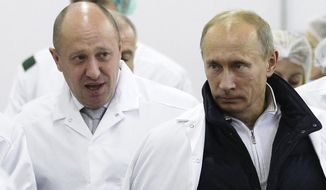 In this Sept. 20, 2010, photo, businessman Yevgeny Prigozhin, left, shows Russian President Vladimir Putin around his facility that produces school meals outside St. Petersburg, Russia. (Alexei Druzhinin/Pool Photo via AP) **FILE**