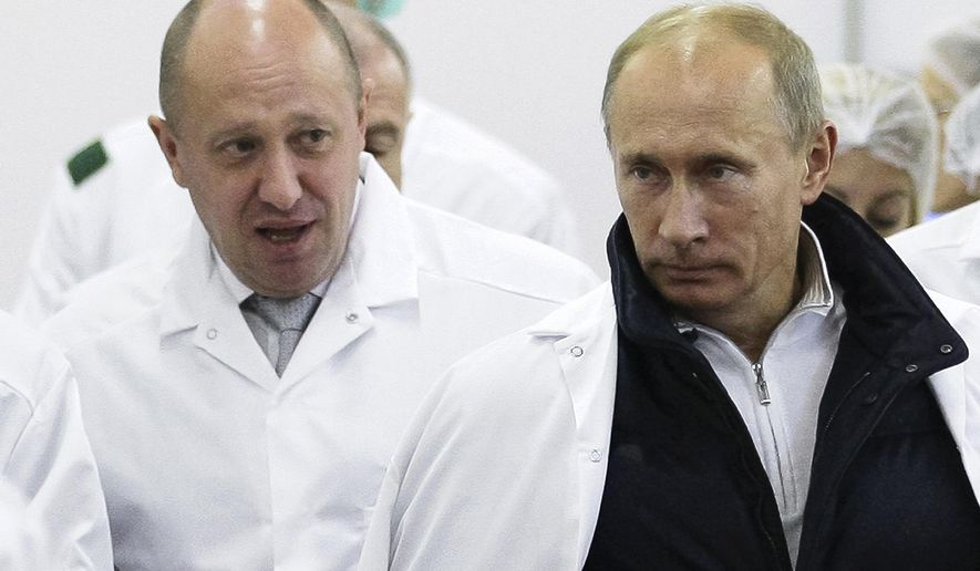 In this Sept. 20, 2010, file photo, businessman Yevgeny Prigozhin, left, shows Russian President Vladimir Putin around his facility that produces school meals outside St. Petersburg, Russia.  (Alexei Druzhinin/Pool Photo via AP, File) **FILE**