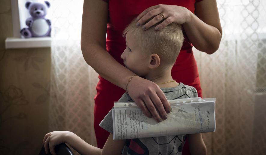 In this photo taken on Monday, March 11, 2019, Natalya Konkova holds her son, Yaroslav, during an interview with The Associated Press in Moscow, Russia. Konkova's son was one of nearly 130 Moscow children who were diagnosed with dysentery after eating food at one of the state-run day care centers and kindergartens in Moscow in December. (AP Photo/Alexander Zemlianichenko)