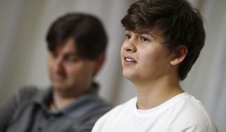 Joshua Jones, front, who was wounded while trying to stop a gunman involved in the attack on the STEM School Highlands Ranch last week, speaks during a news conference as his father, David, listens Tuesday, May 14, 2019, in Littleton, Colo. Jones, Kendrick Castillo and Brendan Bialy tackled the teen who opened fire at STEM School Highlands Ranch south of Denver on May 7. Castillo was fatally shot. (AP Photo/David Zalubowski)