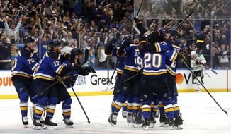 """FILE - In this May 7, 2019, file photo, St. Louis Blues celebrate after defeating the Dallas Stars in double overtime in Game 7 of an NHL second-round hockey playoff series in St. Louis. The Blues won 29 of their final 43 games to go from last place in the NHL to the Western Conference final. They adopted Laura Branigan's song """"Gloria"""" in January after hearing it at a private South Philadelphia bar. (AP Photo/Jeff Roberson, File)"""