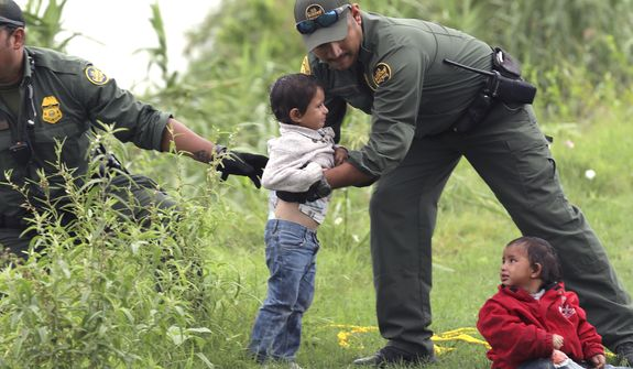 In this Friday, May 10, 2019, file photo, Border Patrol Agents rescue two children from Honduras after their makeshift raft turned over with their mother in it as they were attempting to cross the Rio Grande River near Eagle Pass, Texas. (Bob Owen/The San Antonio Express-News via AP)