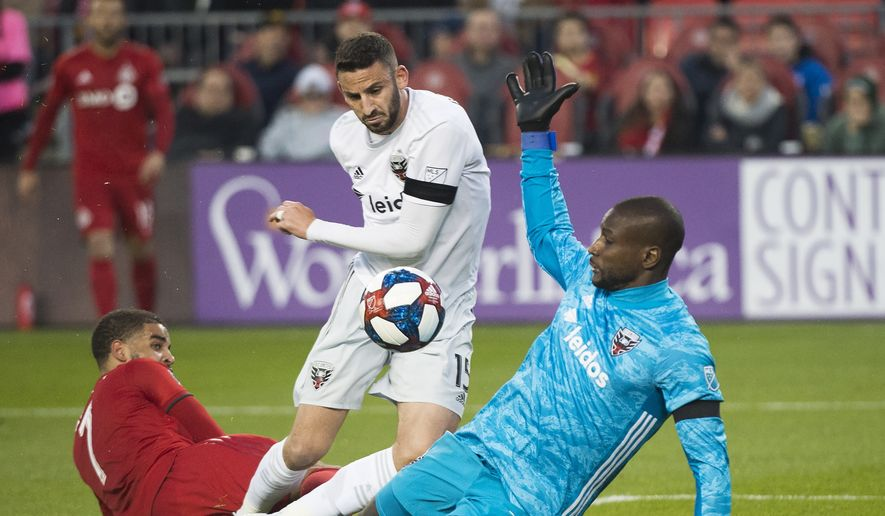 D.C. United goalkeeper Bill Hamid (24) makes a save against Toronto FC forward Jordan Hamilton (7) as D.C. United defender Steve Birnbaum (15) looks on during the first half of an MLS soccer game, Wednesday, May 15, 2019 in Toronto. (Nathan Denette/The Canadian Press via AP) ** FILE **