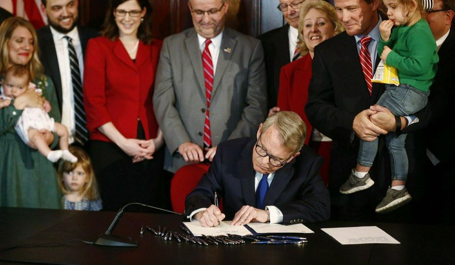 In this April 11, 2019, file photo, Gov. Mike DeWine signs a bill imposing one of the nation's toughest abortion restrictions, in Columbus, Ohio. (Fred Squillante/The Columbus Dispatch via AP, File)