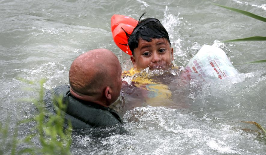 In this Friday, May 10, 2019, file photo, Border Patrol Agent Brady Waikel rescues a 7-year-old boy from Honduras after he fell out of a makeshift raft and lost hold of his mother as Border Patrol agents respond to rafts crossing the Rio Grande River near Eagle Pass, Texas. (Bob Own/The San Antonio Express-News via AP)