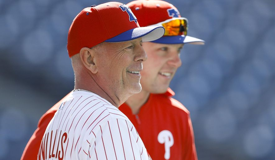 Actor Bruce Willis talks with Philadelphia Phillies' Rhys Hoskins during batting practice before a baseball game against the Milwaukee Brewers, Wednesday, May 15, 2019, in Philadelphia. (AP Photo/Matt Slocum)