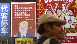 In this Aug. 13, 2018, file photo, a man walks by a poster depicting a mural of U.S. President Donald Trump stating that all American consumers will be charged 25 percent more than others starting from the day Trump started the trade war against China. The poster is on display outside of a restaurant in Guangzhou in south China's Guangdong province. (Color China Photo via AP, File)