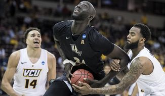 FILE- In this March 22, 2019 file photo, Central Florida center Tacko Fall (24) is fouled by VCU guard Mike'L Simms, right, during the second half of a first-round game in the NCAA men's college basketball tournament in Columbia, S.C. The NBA has picked 11 players from the G League Elite Camp to stay for the NBA draft combine that starts Thursday, May 16. Fall, Florida State's Terance Mann, Miami's Dewan Hernandez, Syracuse's Oshae Brissett, Nevada's Cody Martin, Tulsa's DaQuan Jeffries, Auburn's Jared Harper, Iowa's Tyler Cook, Iowa State's Marial Shayok, Mississippi State's Reggie Perry and Ole Miss' Terence Davis were invited Wednesday, May 15 to stay. (AP Photo/Sean Rayford, File)