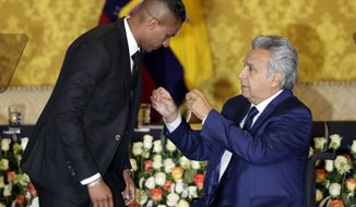 Ecuador's President Lenin Moreno, right, decorates soccer star Antonio Valencia with a National Order of Merit, in Quito, Ecuador, Tuesday, May 14, 2019. The Ecuadorian's final game with Manchester United was Sunday, after 10 seasons with the team. (AP Photo/Dolores Ochoa)