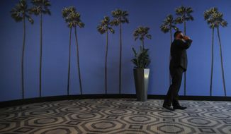 FILE - In this May 4, 2018, file photo a man talks on the phone in a hallway adorned with the palm tree-printed wallpaper at a hotel near the Los Angeles International Airport in Los Angeles. U.S. regulators are proposing new measures intended to thwart billions of annoying robocalls received by Americans each year. The rising volume of unwanted calls in the last few years has created pressure on Congress, regulators and phone companies to do something to act. (AP Photo/Jae C. Hong, File)