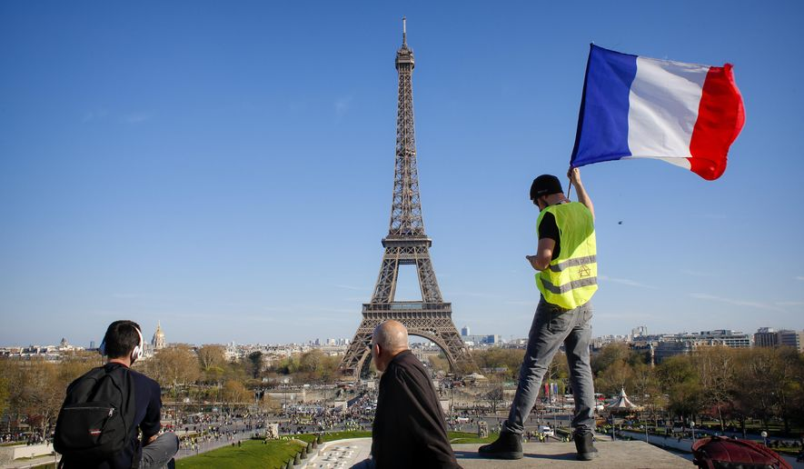 """FILE - In this Saturday, March 30, 2019 file photo, a man holds a French flag as French with the Eiffel Tower in the background, during protests in Paris. Paris is wishing the Eiffel Tower a happy birthday with an elaborate laser show retracing the monument's 130-year history. First, the monument invited 1,300 children to a giant """"snack time"""" Wednesday, May 15 beneath the tower dubbed the Iron Lady. (AP Photo/Thibault Camus, file)"""