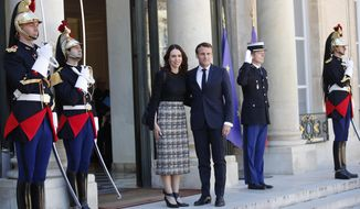 New Zealand Prime Minister Jacinda Ardern, center left, is greeted by French President Emmanuel Macron, center right, as she arrives at the Elysee Palace, in Paris, Wednesday, May 15, 2019. World leaders and tech bosses meet Wednesday in Paris to discuss ways to prevent social media from spreading deadly ideas. (AP Photo/Francois Mori)