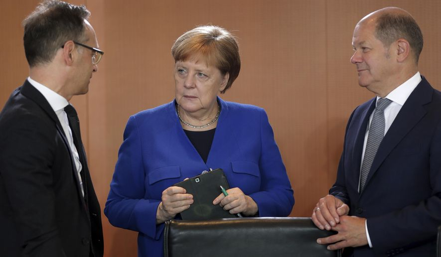 German Chancellor Angela Merkel, center,  German Foreign Minister Heiko Maas, left, and German Finance Minister Olaf Scholz talk as they arrive for the weekly cabinet meeting at the chancellery in Berlin, Germany, Wednesday, May 15, 2019. (AP Photo/Michael Sohn)