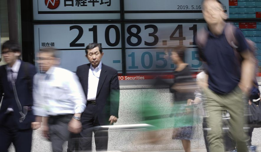 People walk past an electronic stock board showing Japan's Nikkei 225 index at a securities firm in Tokyo Thursday, May 16, 2019. Asian shares were mixed Thursday as worries remained about trade tensions, tempered by media reports that President Donald Trump may delay a decision on auto tariffs. (AP Photo/Eugene Hoshiko)