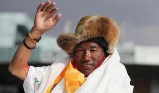 FILE - In this May 20, 2018, file photo, Nepalese veteran Sherpa guide, Kami Rita, 48, waves as he arrives in Kathmandu, Nepal. Rita has scaled Mount Everest for a 23rd time, breaking his own record for the most successful ascents of the world's highest peak. (AP Photo/Niranjan Shrestha, File)