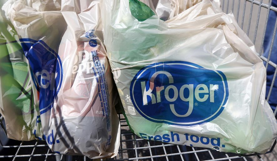 FILE - In this June 15, 2017, file photo, bagged purchases from the Kroger grocery store in Flowood, Miss., sit inside this shopping cart. Grocery delivery services are growing rapidly, but shoppers need to decide if the convenience is worth the higher cost. Grocery chains like Kroger and Safeway are working with third party delivery services like Instacart or developing their own services. (AP Photo/Rogelio V. Solis, File)