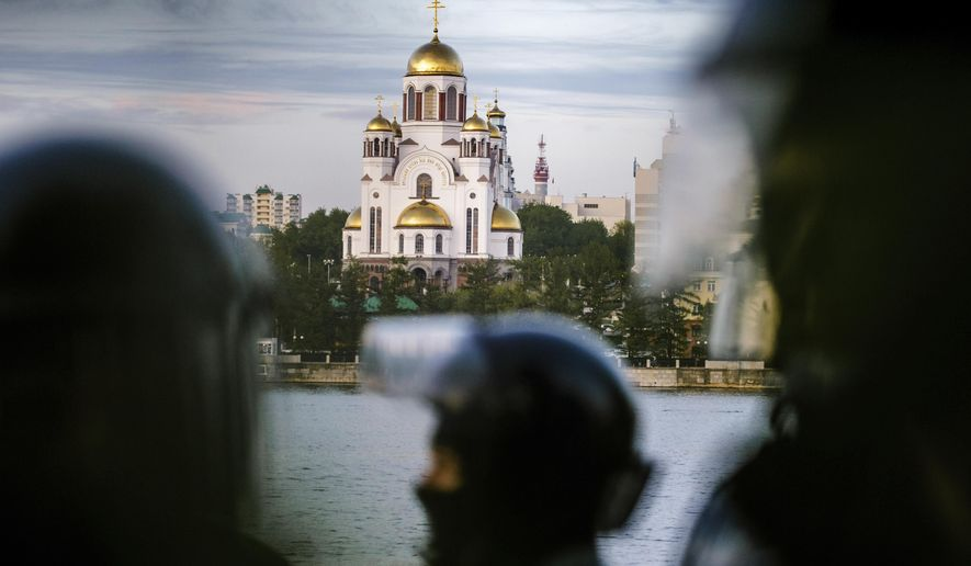 Riot police stand next to demonstrators gather in front of a newly built fence blocked by police, during a protest against plans to construct a cathedral in a park with the Church on the Blood, a cathedral erected on a place where the last czar, his wife Alexandra and their five children were executed in 1918, in Ural Mountain city of Yekaterinburg, background, in Yekaterinburg, Russia, Wednesday, May 15, 2019. Hundreds of riot police have surrounded a park in Russia's fourth-largest city before what's expected to be a third consecutive day of protests against building a new cathedral. (AP Photo/Anton Basanayev)